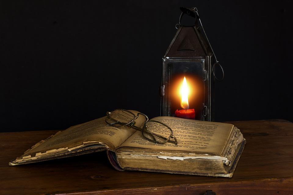 Un vieux livre avec une lanterne à bougie